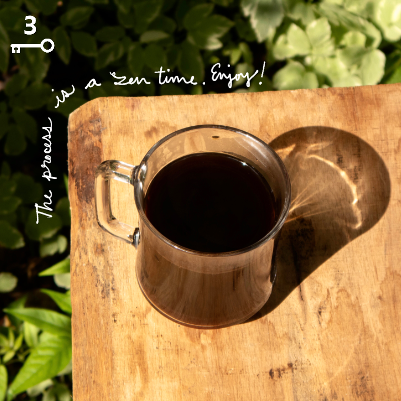"A glass of rich black coffee sitting on a wood table outside with sunlight and shadow, and the text overlay reads, ""The process is a zen time … Enjoy!"""